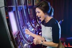La mujer es feliz de su triunfo en máquinas tragaperras imágenes de archivo libres de regalías