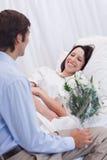 La mujer es feliz sobre la recepción de una visita en el hospital Foto de archivo