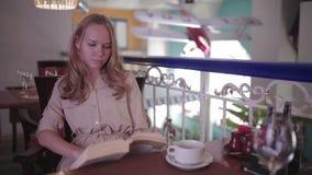La mujer es libro de lectura que se sienta en un restaurante almacen de metraje de vídeo