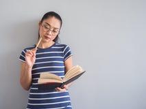 La mujer es libro de lectura y piensa para las ideas foto de archivo