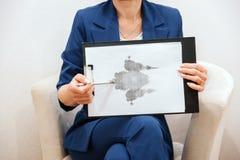 La mujer es que sienta y que lleva a cabo una imagen Es dibujo de la mano Se ata a la tableta La mujer está señalando en imagen fotografía de archivo