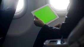 La mujer es que sienta y que sostiene el ordenador portátil inalámbrico moderno con la pantalla táctil y el dispositivo de las au almacen de video