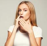 La mujer escoge su finger de la nariz foto de archivo