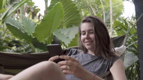 La mujer escribe el mensaje en smartphone mientras que se sienta en la hamaca, fondo natural fotos de archivo libres de regalías