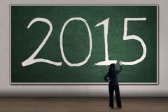 La mujer escribe el número 2015 en la pizarra Imágenes de archivo libres de regalías