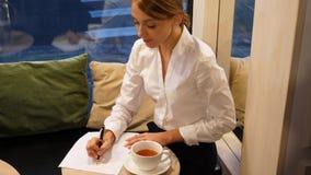 La mujer escribe la letra en café almacen de metraje de vídeo