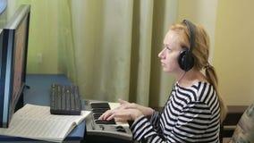 La mujer escribe música en el ordenador teclado digital de Midi del piano almacen de video