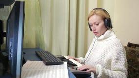 La mujer escribe música en el ordenador teclado digital de Midi del piano metrajes