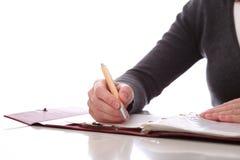La mujer escribe por la pluma en el papel. Aislado Foto de archivo libre de regalías