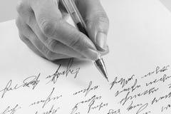 La mujer escribe una letra manuscrita fotos de archivo