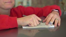 La mujer escribe una orden de la tienda de delicatessen en el contador almacen de metraje de vídeo