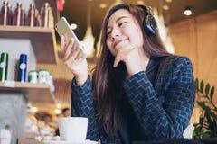 La mujer escucha la música con el auricular Imagen de archivo libre de regalías