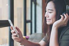 La mujer escucha la música con el auricular Fotos de archivo libres de regalías