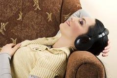La mujer escucha música y relajándose en el sofá Fotos de archivo