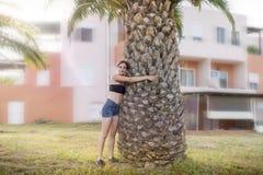 La mujer está abrazando una palmera Fotografía de archivo libre de regalías