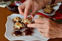 La mujer está adornando las galletas para la Navidad Imagen de archivo libre de regalías