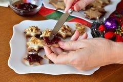 La mujer está adornando las galletas para la Navidad Fotografía de archivo