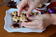 La mujer está adornando las galletas para la Navidad Fotografía de archivo libre de regalías