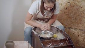 La mujer está amasando la arcilla en el taller de la rueda de alfarero adentro almacen de metraje de vídeo