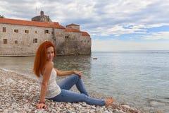 La mujer está asentando en la costa de mar Montenegro Fotografía de archivo libre de regalías
