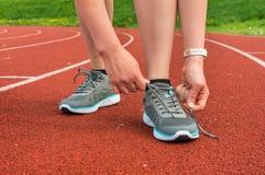 La mujer está atando sus zapatos en una pista corriente del estadio Imagenes de archivo
