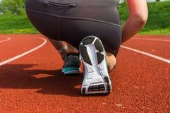 La mujer está atando sus zapatos en una pista corriente del estadio Foto de archivo libre de regalías