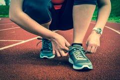 La mujer está atando sus zapatos en una pista corriente del estadio Imagen de archivo libre de regalías