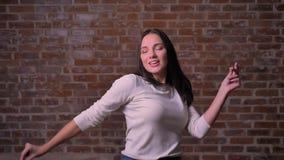 La mujer está bailando vigoroso con sus manos altas en para bricken el fondo almacen de metraje de vídeo