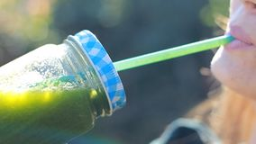 La mujer está bebiendo el primer verde de los smoothies Concepto de detox, dieta, vegetarianismo, forma de vida sana almacen de metraje de vídeo