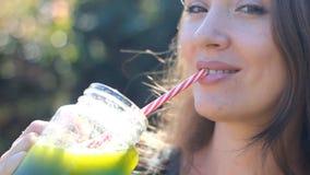La mujer está bebiendo el primer verde de los smoothies Concepto de detox, dieta, vegetarianismo, forma de vida sana metrajes