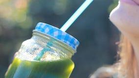 La mujer está bebiendo el primer verde de los smoothies Concepto de detox, dieta, vegetarianismo, forma de vida sana almacen de video