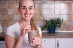 La mujer está bebiendo el smoothie sano fresco del arándano fotografía de archivo