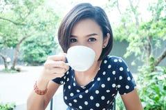 La mujer está bebiendo una taza de café Foto de archivo libre de regalías