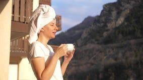 La mujer está bebiendo una taza de té o de café en los rayos del sol en terraza en montañas almacen de metraje de vídeo