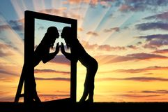 La mujer está besando su reflexión en el espejo imagen de archivo