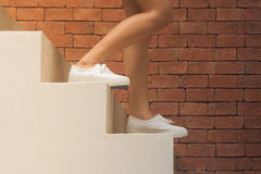 La mujer está caminando abajo de las escaleras concretas blancas afuera en los edificios con el fondo anaranjado del ladrillo Fotografía de archivo libre de regalías