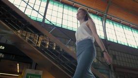 La mujer está caminando con el tren que espera de la maleta para viajar a un viaje de negocios almacen de video