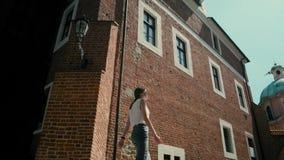 La mujer está caminando en el centro de ciudad histórico en verano con la llamarada agradable de los rayos del sol metrajes
