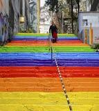 La mujer está caminando en las escaleras arco iris-coloreadas Foto de archivo libre de regalías