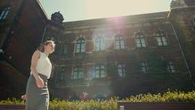 La mujer está caminando a lo largo del edificio histórico con la hiedra en Sunny Summer almacen de video
