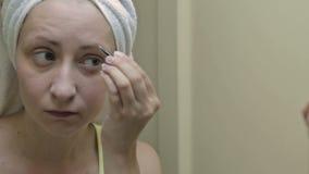La mujer está cepillando el cosmético de la paleta de la sombra de ojos almacen de metraje de vídeo