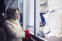 La mujer está cerca del escaparate Imagenes de archivo