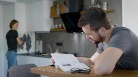 La mujer está cocinando el desayuno para su marido querido por mañana, el hombre se está sentando en la tabla y el libro de lectu almacen de metraje de vídeo