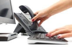 La mujer está cogiendo el teléfono en centro de ayuda Imagenes de archivo