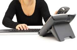 La mujer está cogiendo el teléfono en centro de ayuda Imagen de archivo libre de regalías