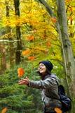 La mujer está cogiendo las hojas que caen Imagen de archivo