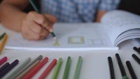 La mujer está coloreando imágenes en un libro con el lápiz coloreado almacen de metraje de vídeo