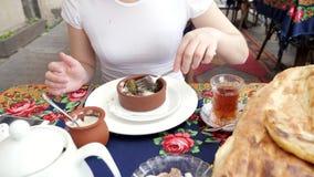 La mujer está comiendo dolma con crema agria en el restaurante tradicional de Azerbaijan almacen de metraje de vídeo