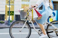 La mujer está completando un ciclo en vestido azul en la bicicleta blanca fotografía de archivo