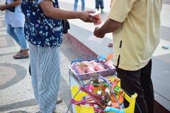 La mujer está comprando el caramelo de algodón a un vendedor tradicional fotos de archivo libres de regalías